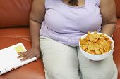 stock photo of crisps  - Woman sitting on couch with magazine and crisps mid section - JPG