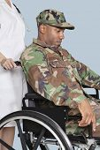 stock photo of corps  - Sad US Marine Corps soldier wearing camouflage uniform in wheelchair assisted by female nurse - JPG