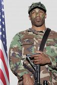 US Marine Corps soldier with  assault rifle standing by American flag over gray background