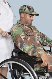 pic of united states marine corps  - Sad US Marine Corps soldier wearing camouflage uniform in wheelchair assisted by female nurse - JPG