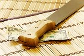 Dollars and knife on wooden mat