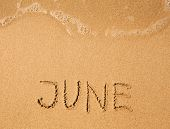 June - written in sand on beach texture (soft wave of the sea)