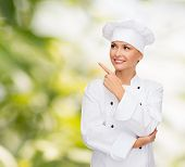 cooking, advertisement and food concept - smiling female chef, cook or baker pointing finger to some