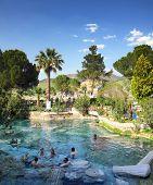 PAMUKKALE, TURKEY - APRIL 30, 2013:Tourists bathing in ancient pool (Cleopatra pool) in Pamukkale Tu