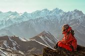 image of mountain chain  - Man sitiing and meditating on the top of mountain in Himalayas with an awesome view to snowy peaks chain - JPG