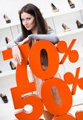 Woman showing the percentage of sales on stylish shoes in the shopping center against the window cas