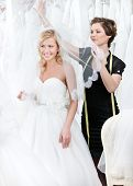 Shop assistant puts wedding veil on the head of the bride, white background