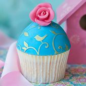 Cupcake decorated with a pink sugar rose