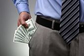 picture of corruption  - Businessman with money in suit trouser pocket concept for business wealth - JPG