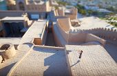 Tourist taking pictures on the roof of building in ancient city of Itchan Kala at sunny day, Khiva,