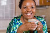 African Woman drinking coffee at home