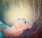 stock photo of glowing  - Beauty Romantic Girl lying on the Field and dreaming - JPG
