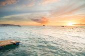 stock photo of boracay  - Sunset in Boracay, Philippines  at the beach, with orange and blue tones and a single boat in the horizon.