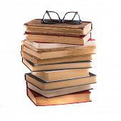 Stack of old antique books and spectacles, isolated on white background.