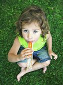 a young girl eating a frozen treat in the grass