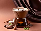 Chocolate fondue with marshmallow candies, on brown background