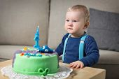 Little baby celebrating its first birthday, in front of him cake with candle in the form of