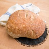 pic of home-made bread  - Fresh home baked loaf of bread on wooden table with white tablecloth and black vintage drying rack - JPG
