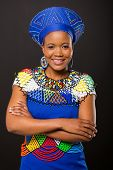 smiling young zulu woman with arm crossed on black background