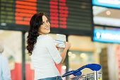 beautiful young woman holding passport and boarding pass in front of flight information board at airport