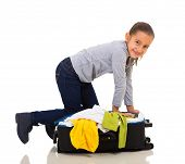 pretty little girl packing suitcase for vacation