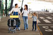 happy traveling family with suitcases at airport