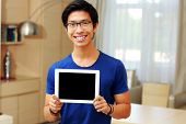 Young happy asian man showing tablet computer screen at home