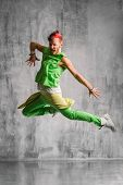 trendy style dancer jumping on studio background