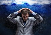 Young businessman under rain covering head with hands