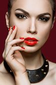 Beautiful woman with evening make-up and red nails with thorns.