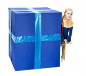 Adorable little girl playing peek-a-boo behind a big blue surprise box