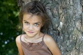 Portrait of beautiful little girl, against background of summer park