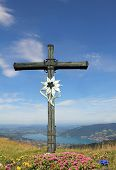 picture of edelweiss  - Wooden mountain cross with edelweiss and alpine flowers view to bavarian lake tegernsee german landscape - JPG