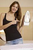 young brunette woman ironing shirt on ironing board