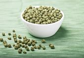 foto of peppercorns  - Dried green peppercorns in a white porcelain bowl on green textile made of linen - JPG