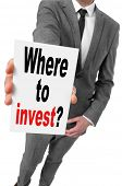 businessman showing a signboard with the text where to invest? written in it