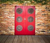 picture of climber plant  - red wooden door on brick wall with climber plant and wooden plank floor - JPG