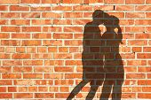 Kissing Silhouette Couple Against Red Brick Wall