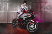 Powerful brunette woman wearing latex mounted on a motorcycle with a modern design