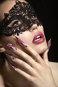 Beautiful girl in a mask with long fingernails.