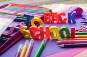 Many school stationery in a heap in the middle of Back to School subtitles