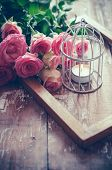 picture of caged  - Bouquet of pink roses wooden frame and a burning candle in a white decorative bird cage on old board background vintage decor and color tinting - JPG