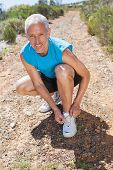 Smiling jogger tying his shoelace on mountain trail on a sunny day