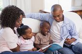 Happy family sitting on couch together reading book at home in the living room