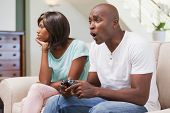 Bored woman sitting next to her boyfriend playing video games at home in the living room
