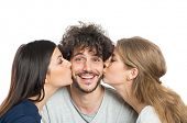 Young Beautiful Women Kissing Man On Cheeks Isolated On White Background