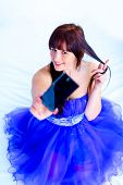A young girl in a blue evening dress poses for the camera cell phone self-portrait with emotions