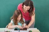 Teacher Assisting Girl In Using Digital Tablet