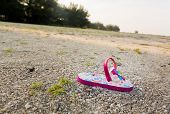 stock photo of kidnapped  - Concept image of the threat for child kidnapping or Amber alert with a single toddlers sandal alone on large beach with no sign of anyone - JPG