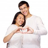 Young smiling interracial couple in love making heart shape with hands isolated on white background